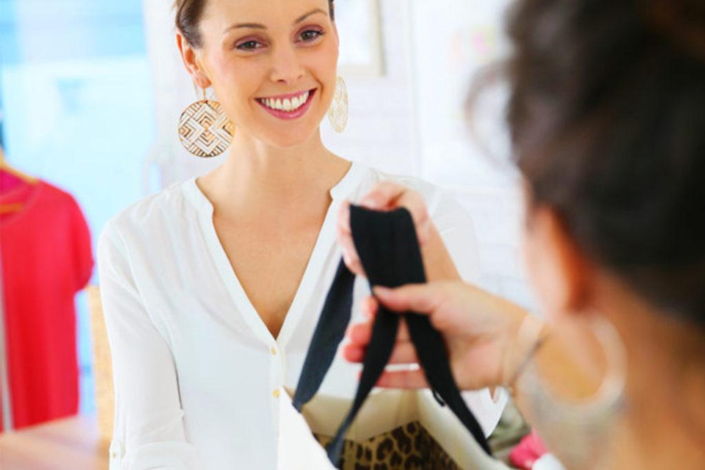 Vendeuse souriante donnant un sac à une cliente