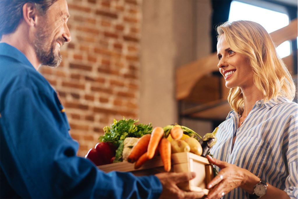 homme donnant une cagette de légumes à une femme souriante