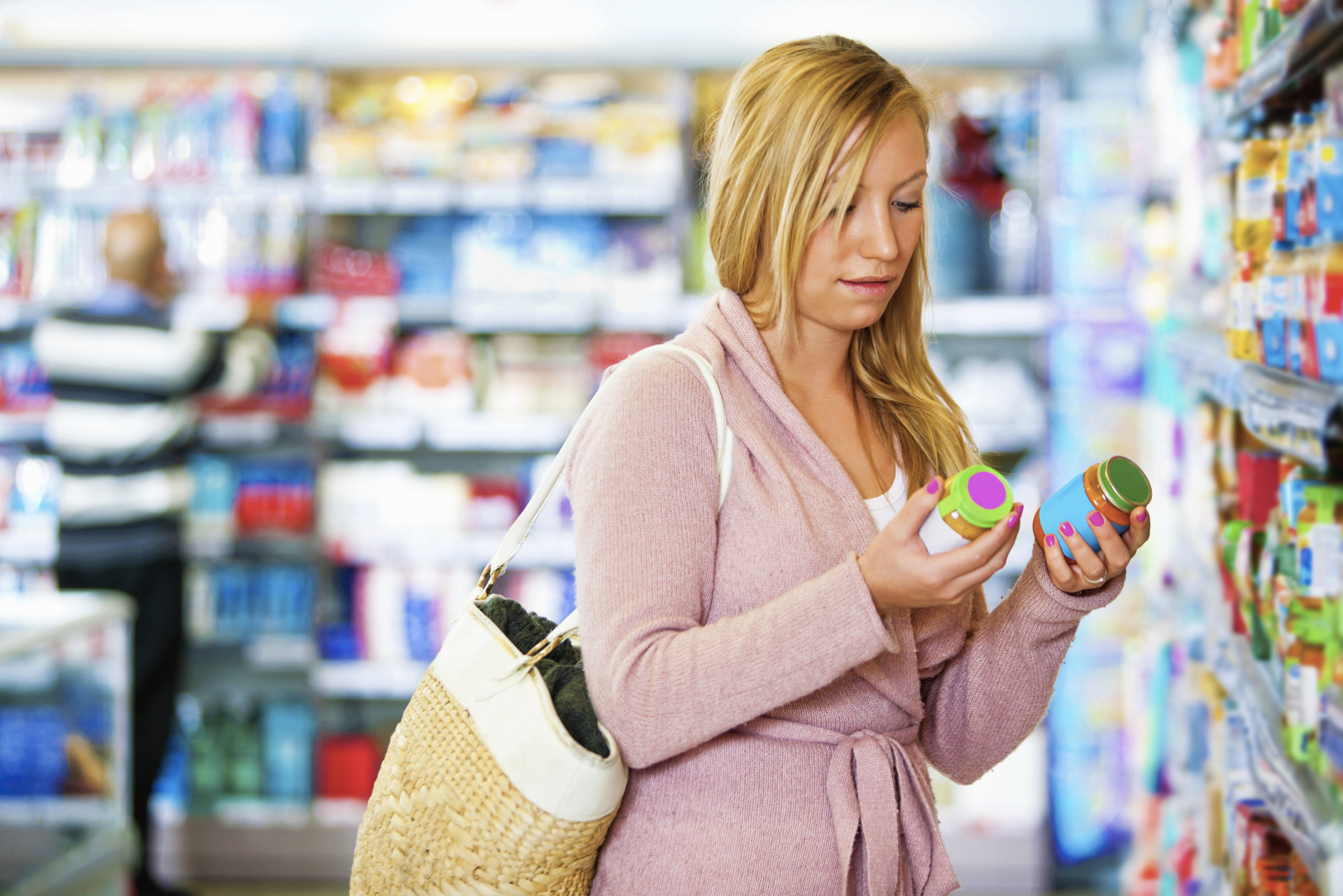 Young woman holding jar in the supermarket