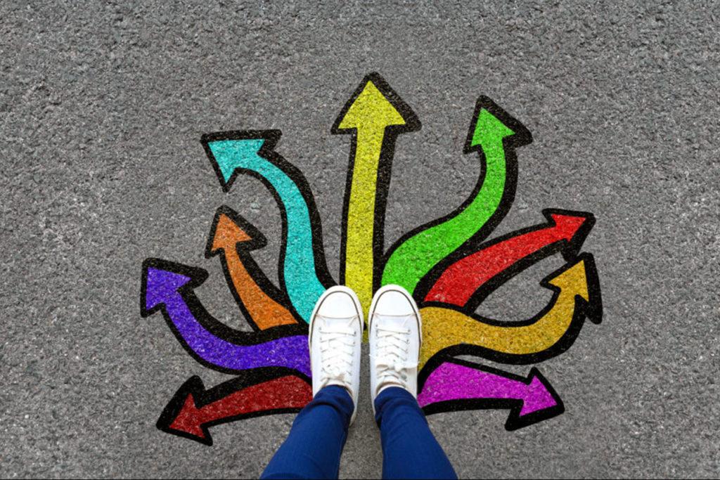photo plongée de pieds sur des tags au sol représentant des flèches de couleur partant dans différentes directions