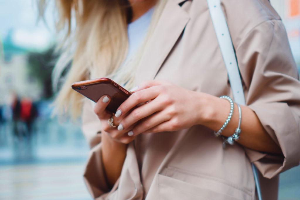 femme dans la rue regardant son téléphone