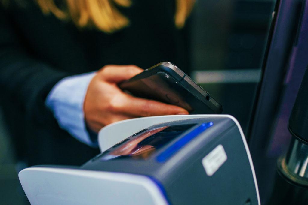 homme payant sur un terminal mobile