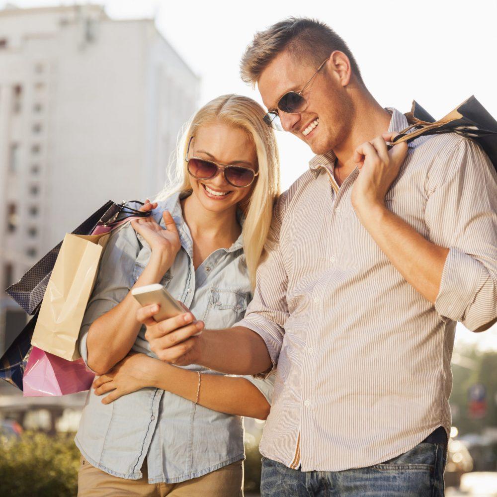 Couple faisant du shopping regardant un téléphone